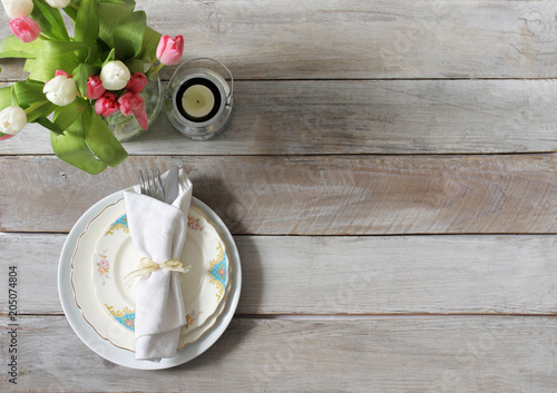 Reserved dinner table with crockery and decor items