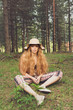 Beautiful bohemian blonde woman in forest, sitting and posing. Natural lighting, no retouch, matte filter.