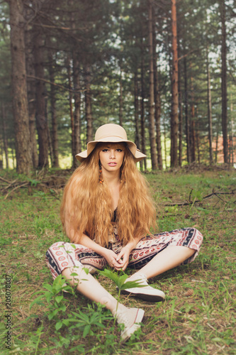 Beautiful bohemian blonde woman in forest, sitting and posing. Natural lighting, no retouch, matte filter. - 205078087