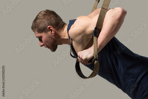 Side view image of strong and healthy man training on bodybuilder. Sport concept.