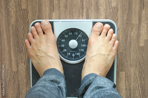 Leinwanddruck Bild Male on the weight scale for check weight, Diet concept