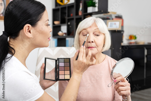 Impressive look. Concentrated volunteer using brush and senior woman rising mirror