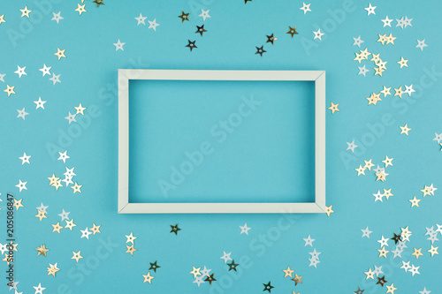 White picture frame and sequins stars on blue background. Top view, flat lay. Mockup for party or birthday invitation.