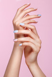 Beautiful pink and blue manicure with crystals on female hand. Close-up. Picture taken in the studio - 205087832