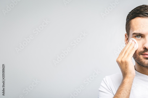 Handsome man cleaning face skin with batting cotton pads over gray background and looking at camera. Close-Up. Space for text.