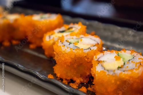 Plexiglas Sushi bar California maki sushi roll on black plate, japanese food
