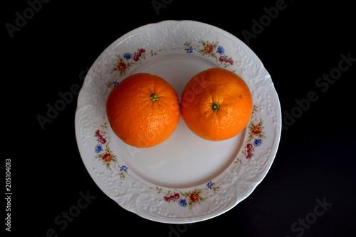 Dos naranjas en un plato.