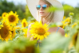 beautiful young woman in a hat and glasses on a field of sunflowers