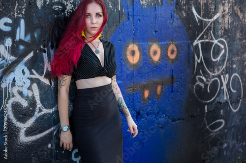sexy redhair woman in hooligan outfit and sunglasses posing against graffiti wall