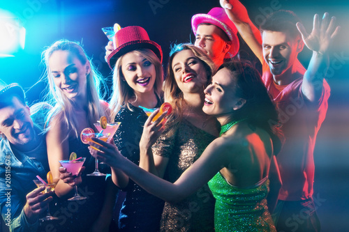 Dance party group people dancing. Women and men have fun in night club. Rest after hard day at work. Back light on girls hair. People dance under influence of alcohol. Toning and blur for background