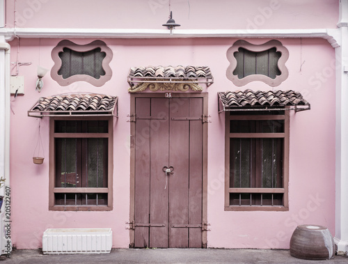 Ancient, pink building with a wooden door - 205122407