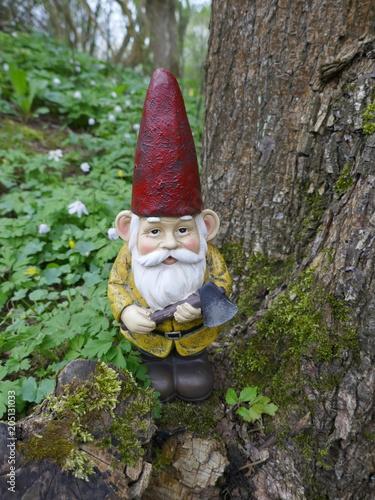 Fotobehang Betoverde Bos Gartenzwerg mit rotem Hut, gelber Jacke, braunen Stiefeln. Er hat eine Axt in der Hand und lehnt sich an einen alten Baumstamm.