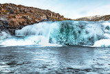 Frozen waterfall on the river in winter on the way from Seyðisfjörður to Skálanes, Iceland