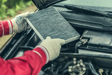 The auto mechanic replaces the car's interior filter.