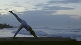 Side view of woman in white leggings and top performing standing split yoga pose on beach in morning - 205148269