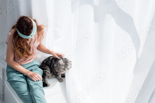 high angle view of young woman petting adorable tabby cat while sitting on windowsill