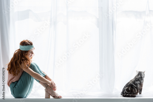 attractive young woman sitting on windowsill with cute tabby cat