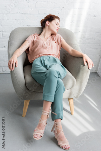 beautiful young woman relaxing on armchair at home