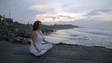 Side view of peaceful woman in white sitting in lotus pose on stone dock near ocean and meditating at sunrise - 205153431