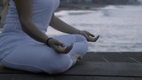 Medium shot of unrecognizable woman in white sitting in lotus pose and meditating near ocean in morning - 205153443