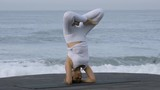 Medium shot of flexible mature woman doing handstand splits and lotus pose on coastline - 205154807