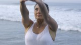 Medium shot of mature woman in white standing in prayer position, then stretching her side on coastline near ocean - 205154869