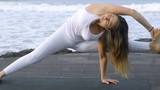Medium shot of mature woman in white practicing yoga on coastline near ocean: she doing splits and holding her leg - 205161882