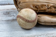 Close up of a used baseball and mitt on white vintage wooden background