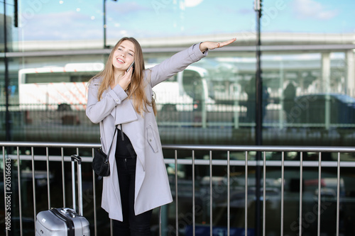 Female person stopping taxi with valise and talking by smartphone near airport. Concept of business trip and advantageous tariff plan.