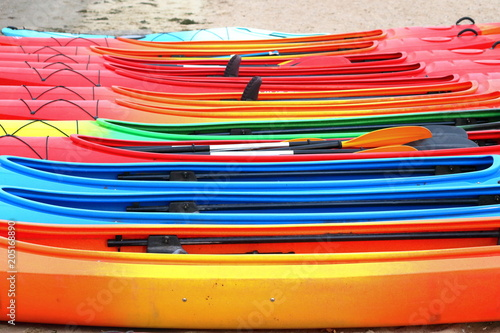 Many bright colored kayaks on sand shore at autumn cloudy day - 205168890