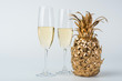 glasses of champagne and golden pineapple on white