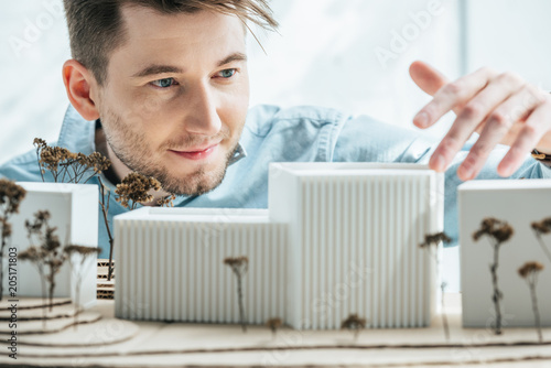 Fototapeta selective focus of smiling architect looking at self made building model in office