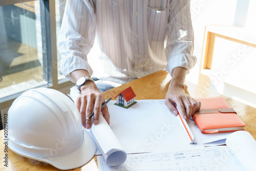 Fototapeta Architect or engineer working on blueprint at workplace on wooden desk. - architectural project, Construction concept.