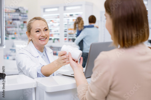Foto Spatwand Apotheek Help customer. Glad female pharmacist assisting woman and grinning