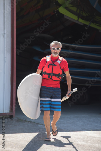 man holding stand up paddle board walking towards the water