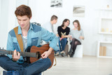 young man playing a guitar - 205186630