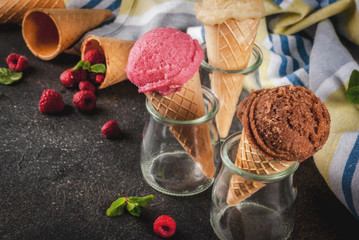 Summer sweet berries and desserts, various of ice cream flavor in cones pink (raspberry), vanilla and chocolate with mint on dark background copy space