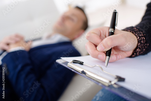 close up of hand of psychotherapist taking notes patient blurred