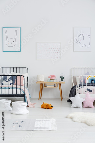 Wooden table between black and white bed in children bedroom interior with posters. Real photo