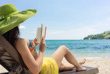 Side view of a young beautiful woman reading a book while sitting on a wooden lounge chair at the beach in a sunny day during summer vacation in Flores Island, Indonesia