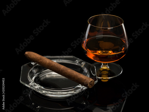 Cognac and cigar in a glass ashtray