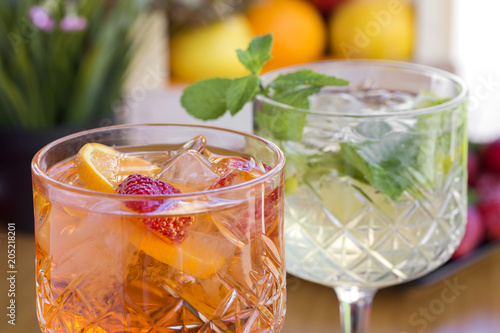 Two cocktails with vodka, strawberries, mint and lemon in glasses on the bar
