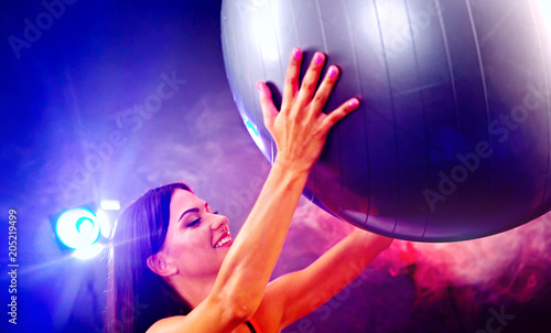 Wall mural Fitness girl exercising in gym with big blue ball. Woman with fitball works in multi-colored rays of sport room. Portrait in profile with lens flare. Aerobics slimming program.