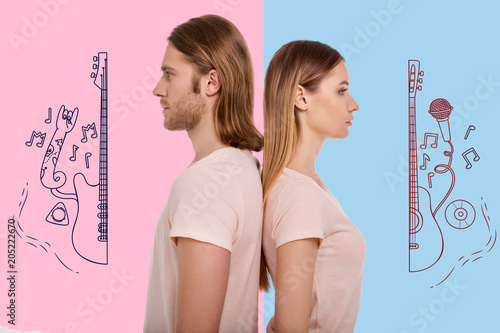 Music fans. Young serious couple standing behind each other and looking thoughtful after a quarrel about music