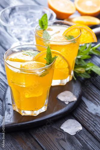 pomarańczowy koktajl z lodu i świeżej mięty na czarny drewniany stół