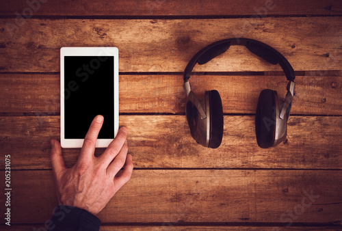 Canvas Muziek A top view of a set of wireless headphones and controlling a blank tablet lying on a rustic wood table, desk. Styling and grain effect added to image.