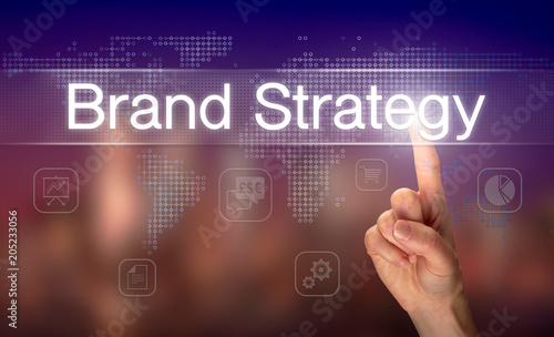 Wall mural A hand selecting a Brand Strategy business concept on a clear screen with a colorful blurred background.