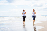 Two women running on beach - 205237246