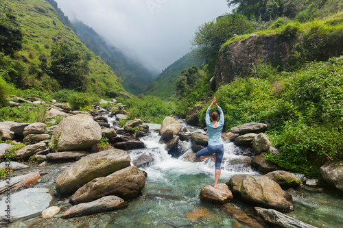 Woman in yoga asana Vrikshasana tree pose at waterfall outdoors - 205242207
