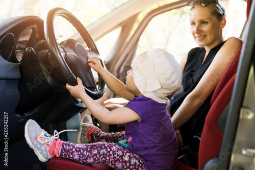 Wall mural mother with child playing in the car steering wheel